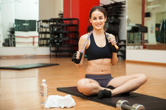Beautiful girl with a jump rope at the gym. Pretty athletic young brunette holding a jump rope at the gym and smiling Royalty Free Stock Images