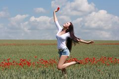 Beautiful girl jumping in a field with poppies. Beautiful girl having fun jumping in a field with poppies enjoying nature Stock Image