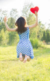Beautiful girl jumping. Holding a heart in his hands. On nature Royalty Free Stock Photography