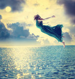 Beautiful girl jumping into the night sky. Beautiful girl jumping into the blue night sky over the ocean Royalty Free Stock Images