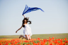 Beautiful girl jumping in the poppy field Royalty Free Stock Image