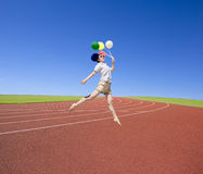 Beautiful girl jumping on red track with balloon Stock Photo