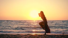 Beautiful girl jumping on the sea coast at sunrise