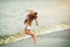 Beautiful girl jumping  through the waves Royalty Free Stock Photography