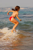 Beautiful girl jumping in the waves on the beach Royalty Free Stock Photography