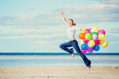 Beautiful girl jumps on the beach while holding Royalty Free Stock Image