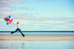 Beautiful girl jumps on the beach while holding Stock Image