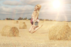 Beautiful girl jumps in sloping field Royalty Free Stock Photography