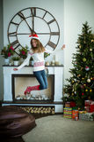 Beautiful girl jumps up near christmas tree Stock Images