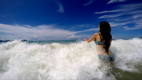 Beautiful girl jumps up and waves hit, slow mo stock video