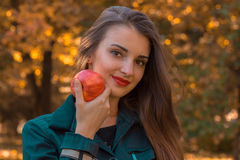 Beautiful girl keeps the Big Apple in his hand looks straight and smiling close-up Stock Photography