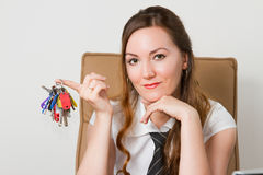 Beautiful girl with the keys in the office Royalty Free Stock Photos