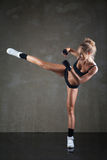 Beautiful girl kicking with the leg on dark grey Stock Image