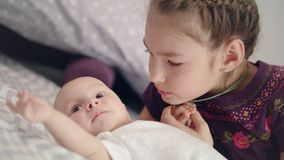 Beautiful girl kissing baby lying on sofa. Sister kiss newborn brother stock video footage