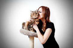 Beautiful girl kissing her cat on neutral background. Beautiful girl kissing her cat on white background. People and pets. Lifestyle Royalty Free Stock Images