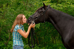 A Beautiful girl kissing her handsome horse. Young beautiful girl kissing her handsome black horse Stock Photography