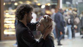 Beautiful girl kissing hugging and talking with her boyfriend in public center using caressing and romantic gesture. Blonde beautiful girl kissing hugging and stock footage