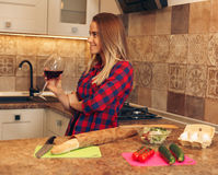 Beautiful girl in the kitchen with a glass of wine. The girl is going to cook dinner, resting Stock Images