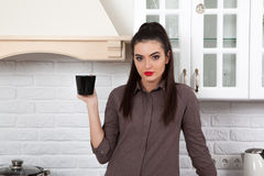 Beautiful girl in the kitchen. The girl in the kitchen at home drinking a cup of tea or coffee, and looking at the camera Royalty Free Stock Photo