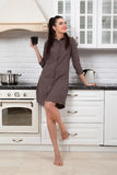 Beautiful girl in the kitchen. Smiling young woman having a cup of coffee at home Royalty Free Stock Photo