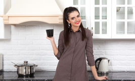 Beautiful girl in the kitchen. Smiling young woman having a cup of coffee at home Stock Photos