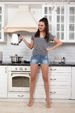 Beautiful girl in the kitchen. Young beautiful slim girl standing in the kitchen preparing coffee. A girl holding a kettle of boiling water. and looks to the Stock Photography