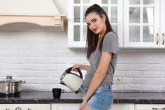 Beautiful girl in the kitchen. Young beautiful slim girl standing in the kitchen preparing coffee. A girl holding a kettle of boiling water, looks to the camera Stock Photo