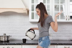 Beautiful girl in the kitchen. Young beautiful slim girl standing in the kitchen preparing coffee. A girl holding a kettle, looks at the cup and drain the hot Stock Photo
