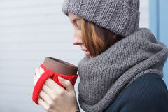 Beautiful girl in a knitted cap and mittens freezing in winter Royalty Free Stock Photography