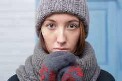 Beautiful girl in a knitted cap and mittens freezing in winter Stock Photos