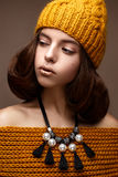 Beautiful girl in a knitted hat on her head and a necklace of pearls around her neck. The model with gentle make-up and gold lips Royalty Free Stock Images