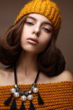 Beautiful girl in a knitted hat on her head and a necklace of pearls around her neck. The model with gentle make-up and gold lips. Beautiful face. Photo taken Stock Photography