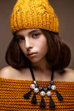 Beautiful girl in a knitted hat on her head and a necklace of pearls around her neck. The model with gentle make-up and gold lips. Beautiful face. Photo taken Royalty Free Stock Image