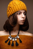 Beautiful girl in a knitted hat on her head and a necklace of pearls around her neck. The model with gentle make-up and gold lips Royalty Free Stock Photography
