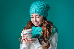 Beautiful girl in a knitted hat holding a cup of coffee Royalty Free Stock Image