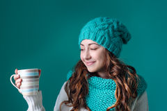 Beautiful girl in a knitted hat and a mug in the studio Stock Image