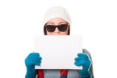 Beautiful girl in a knitted hat and sunglasses smiling and holdi Royalty Free Stock Photography