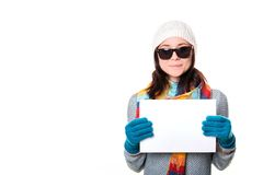 Beautiful girl in a knitted hat and sunglasses smiling and holdi Royalty Free Stock Images