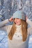 Beautiful girl in a knitted hat. For a walk in the winter forest Royalty Free Stock Photo