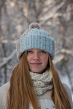 Beautiful girl in a knitted hat. For a walk in the winter forest Stock Images