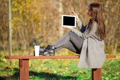 Beautiful girl with laptop in autumn park outdoors Stock Photography