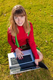Beautiful girl with a laptop on the grass Royalty Free Stock Photo