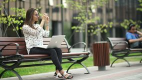 Beautiful girl with a laptop sitting on the street. Remote work. stock footage