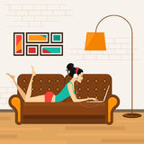 Beautiful girl with laptop on sofa Stock Photos