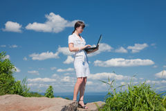Beautiful girl with a laptop is on the stone Royalty Free Stock Image
