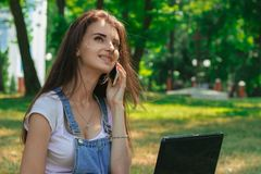 Beautiful girl with a laptop in the summer Park says on the phone Royalty Free Stock Photo