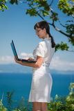 Beautiful girl with a laptop in a tree Stock Images