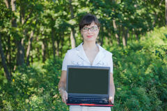Beautiful girl with a laptop is in the woods Royalty Free Stock Photos