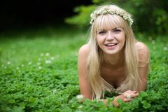 Beautiful Girl Laughing. Summer. Portrait of  blonde girl with blue eyes having rest at clover meadow Stock Image