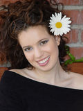 Beautiful girl laughing. A beautiful girl laughing against brick wall with a big daisy in her hair Stock Images